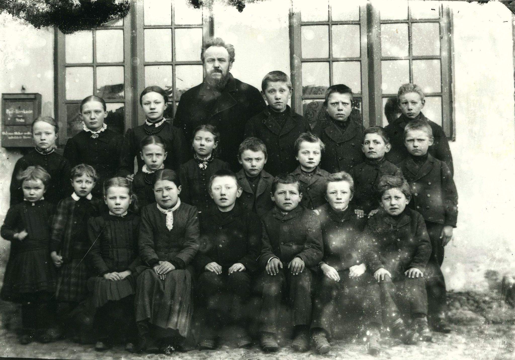 En skoleklasse. Hvor? Lærer Julius Bohn? (det står der på kortet). De har fået fint tøj på, børnene, fordi de skulle fotograferes og pigerne sidder til den ene side, drengene til den anden. Nogle af pigerne er meget små. Glaspladen er desværre noget medtaget - men billedet, motivet er fint. Foto Kjøller, Allinge.