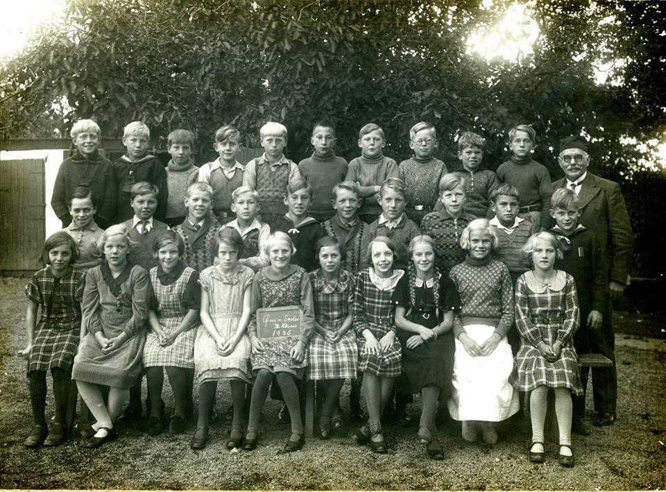 """Fotografen er Kaare Rasmussen, Rønne. På tavlen, som pigen i midten har på skødet står: """"Øm. n. Skole, III Klasse, 1936. (Østermarie nordre Skole). Skolebilledet har tilhørt H.V. Jørgensen, som sikkert er en af drengene på billedet. Bornholms Ø-arkiv."""